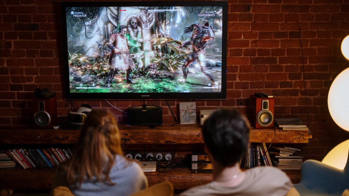 Para siedząca przed telewizorem dla gracza