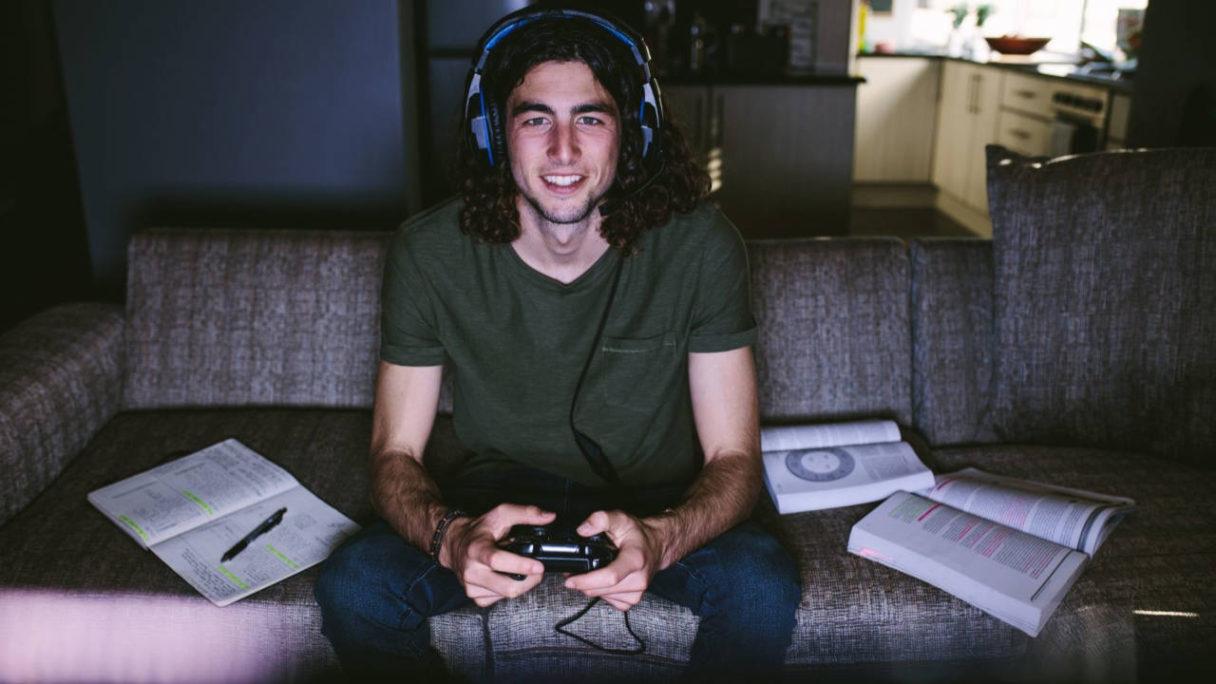 Edukacja Gamingowa - student na kanapie gra w grę, a obok niego otwarte książki