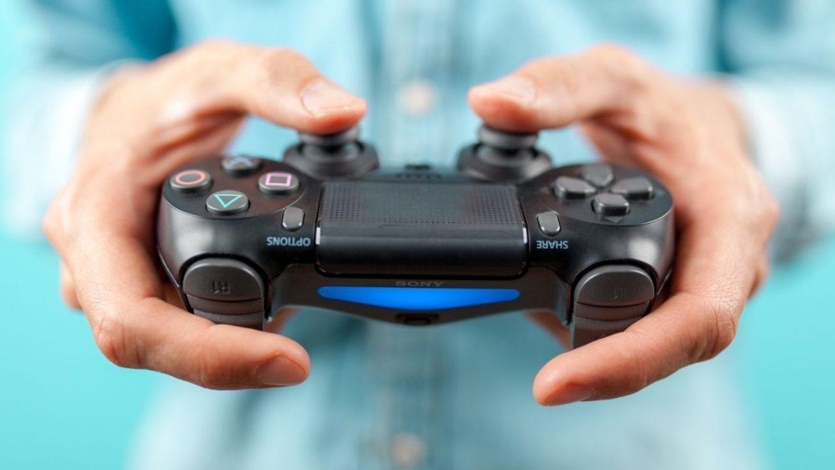 Activision - Mężczyzna trzyma w rękach pada od PS4