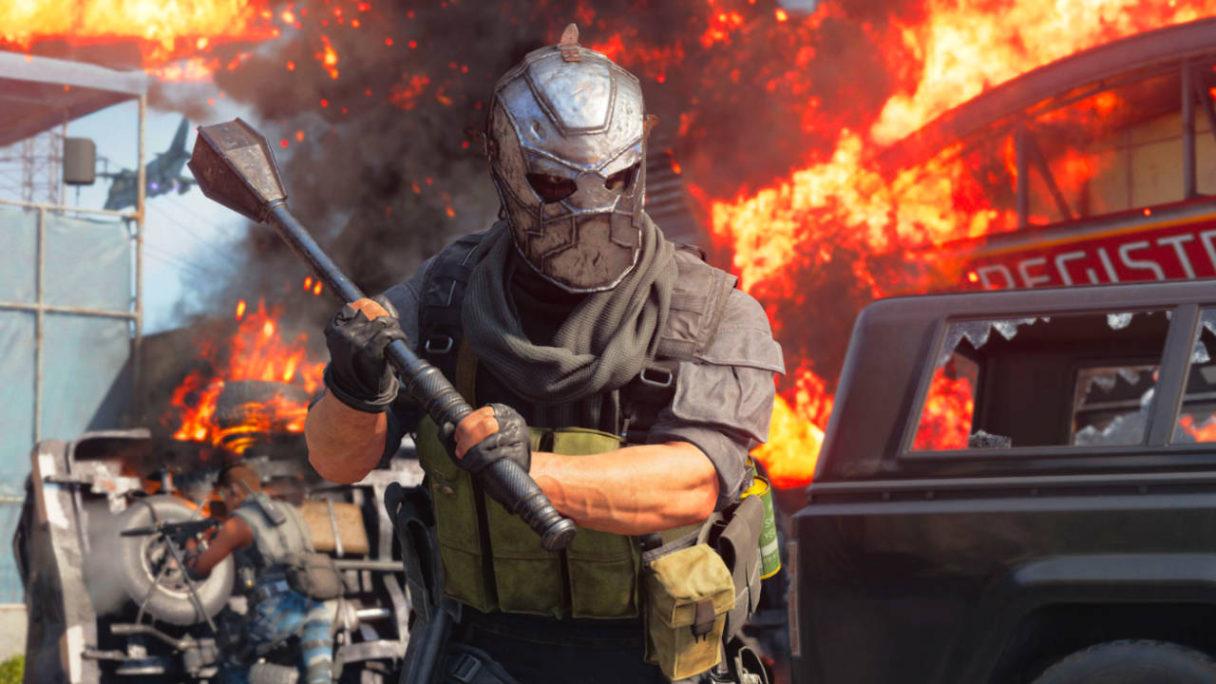 Call of Duty Black Ops Cold War - mężczyzna w masce z wielkim, stalowym obuchem na tle płomieni