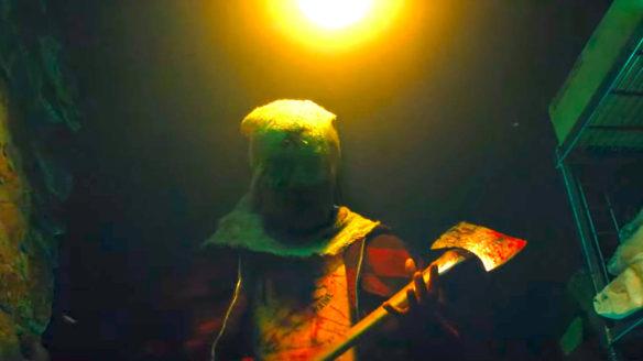 Fear Steet Part 2 1978 - mężczyzna z workiem na głowie i zakrwawioną siekierą w ciemnym pomieszczeniu