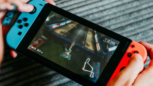 Nintendo Switch Joy Cony neon red/blue- mężczyzna gra w Mario Kart i dobrze mu idzie