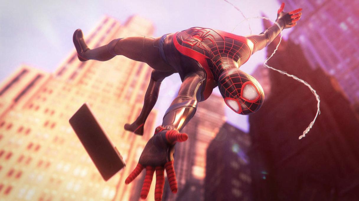 Spider-Man Miles Morales - bohater buja się na pajęczynie i próbuje złapać telefon