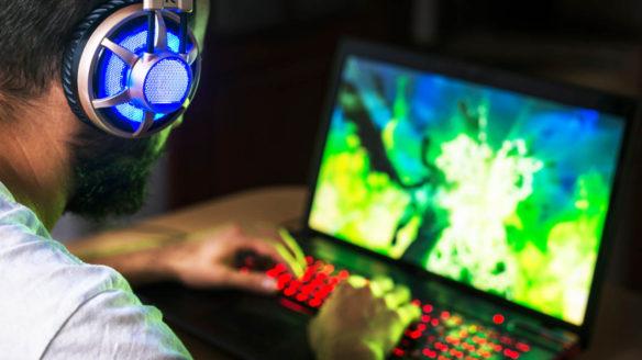 Tani laptop dla gracza - mężczyzna korzystający z gamingowego laptopa