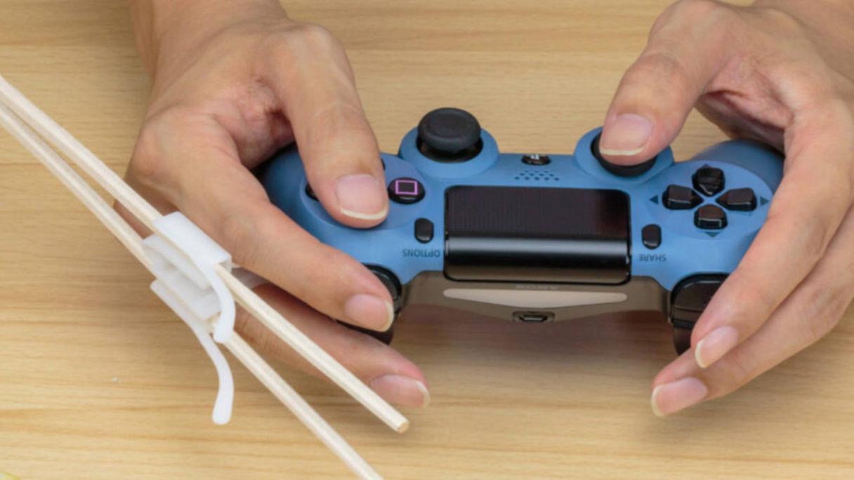 Akcesoria dla graczy - japanese gaming chopsticks - gracz gra na DualShock 4 i ma w ręce gamingowe pałeczki