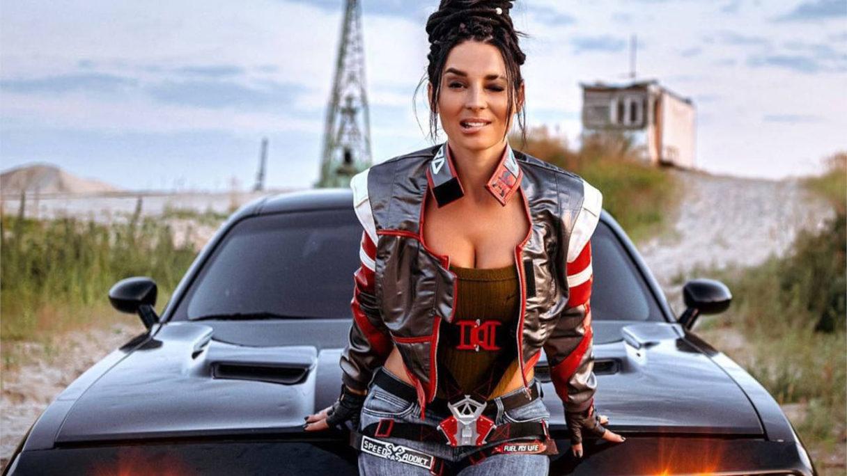 Cyberpunk 2077 - Anna Shakh jako Panam Palmer opiera się o auto i zmysłowo przygryza wargę