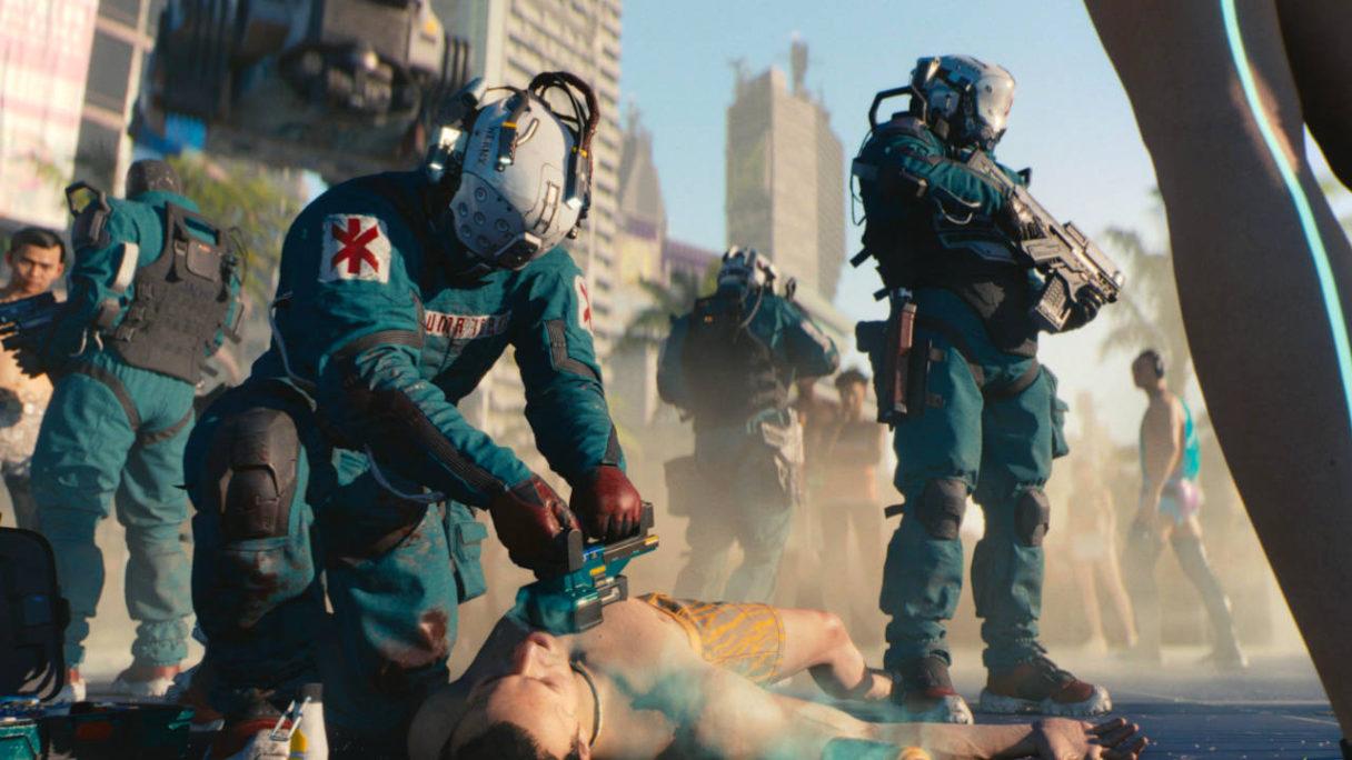 Cyberpunk 2077 - medycy reanimują mężczyznę na ulicy, wokół zebrała się masa gapiów