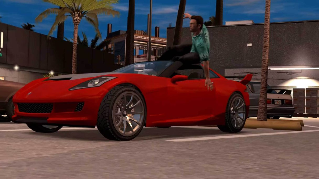 Mężczyzna w niebieskiej koszuli wskakuje przez okno do czerwonego sportowego samochodu
