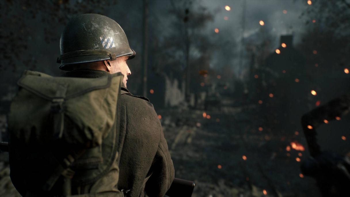 Żołnierz stojący i patrzący się na zniszczony dom