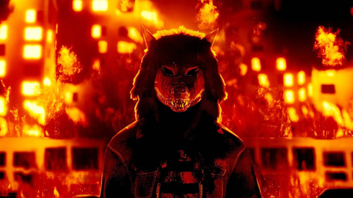 NEON BEASTS - ktoś w przebraniu wilka na tle podpalonych budynków