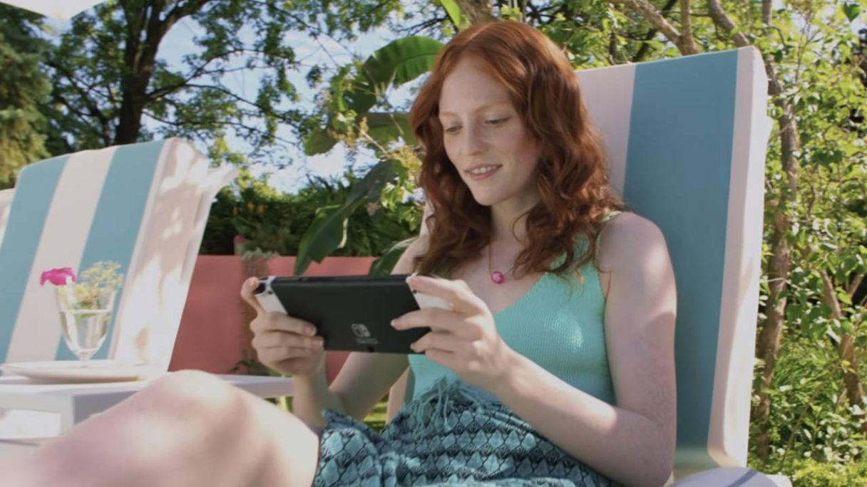 Ruda dziewczyna gra na Nintendo Switch OLED na świeżym powietrzu