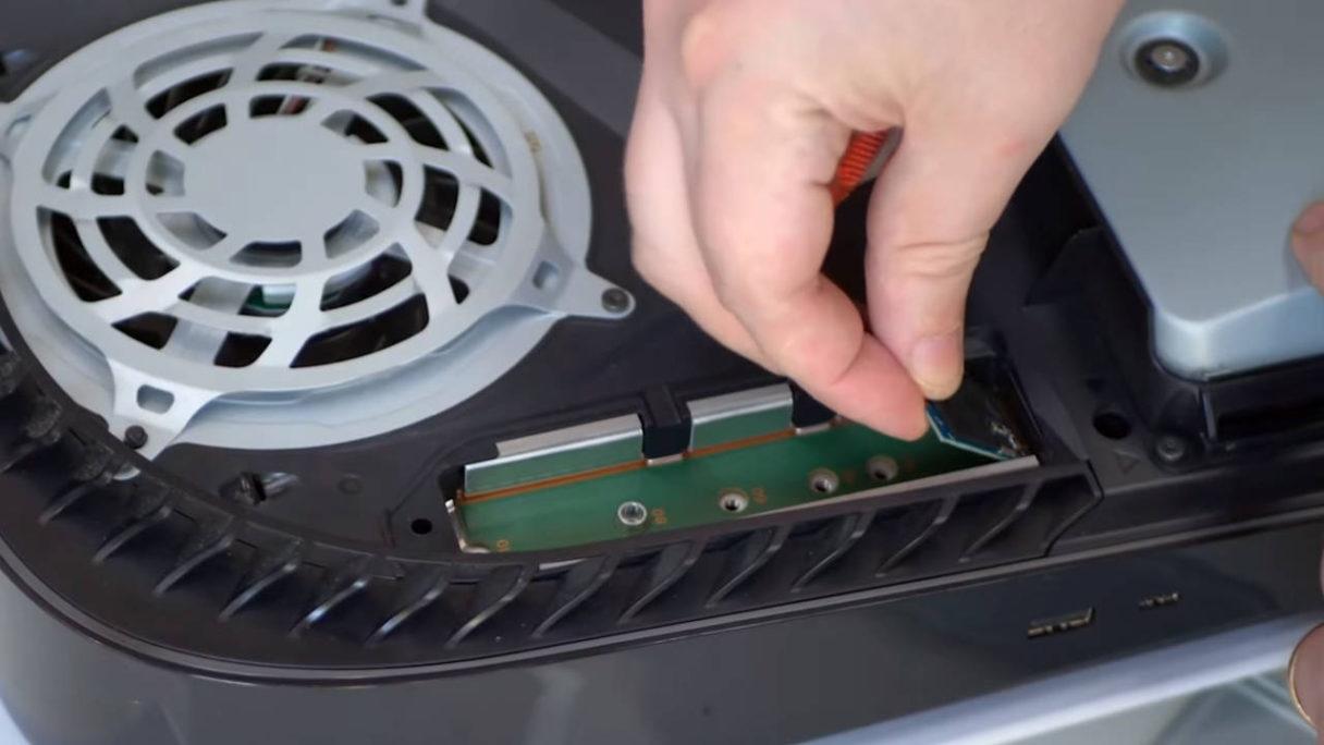 Mężczyzna wsadza dysk SSD z Xbox Series S do konsoli PS5