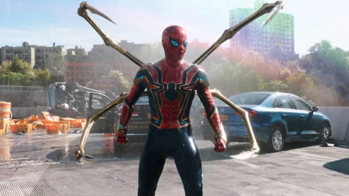 Spider-Man No Way Home - Peter Parker w stroju Iron Spider Suit stoi na moście, w tle tęcza