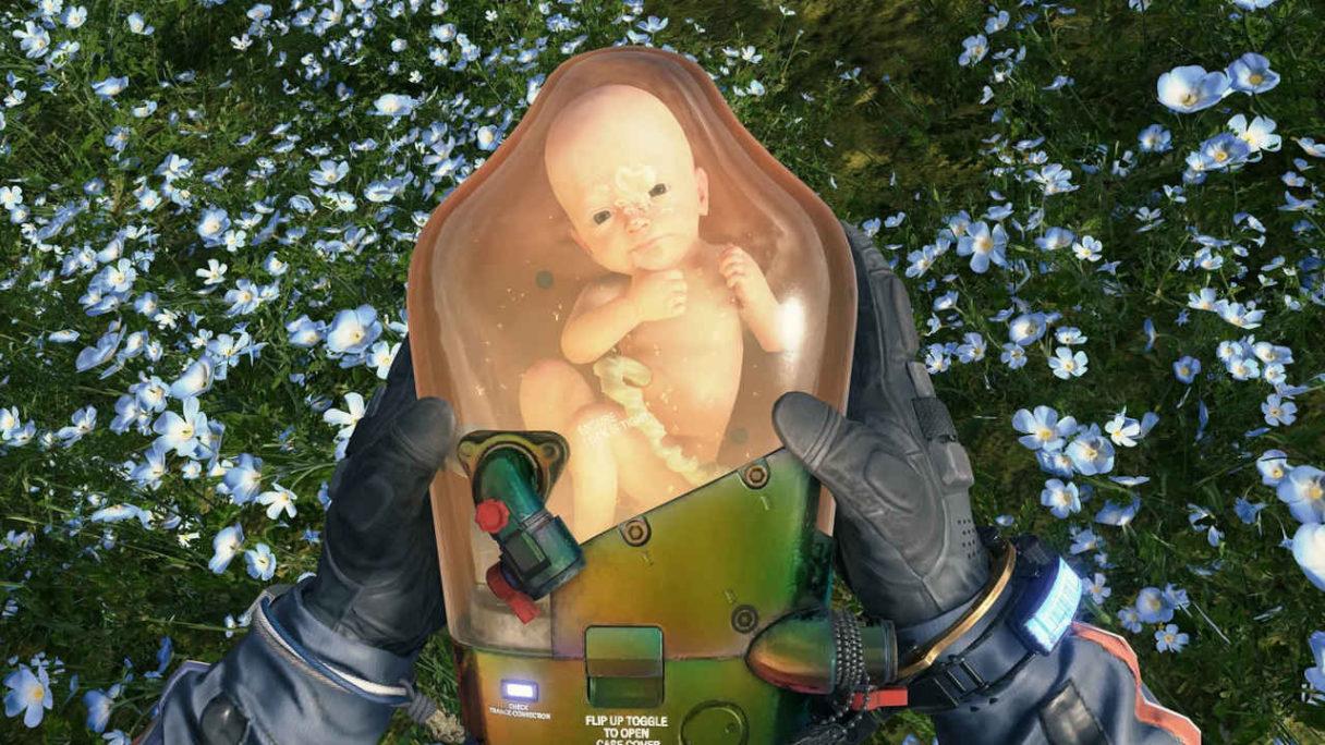 Death Stranding Director's Cut - dziecko w pojemniku trzymane w rękach przez gracza na tle ładnych, niebieskich kwiatów