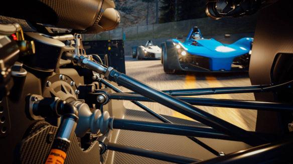 Gran Turismo 7 - Kadr na niebieski samochód wyścigowy podczas wyścigu z perspektywy tylnej osi innego samochodu przed nim- PG