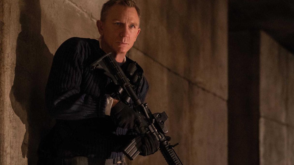 Daniel Craig uzbrojony w karabin szturmowy.