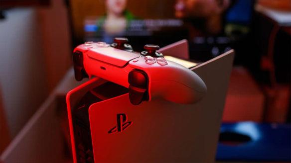 Konsola PlayStation 5 z kontrolerem DualSense w odbiciu czerwonego światła.
