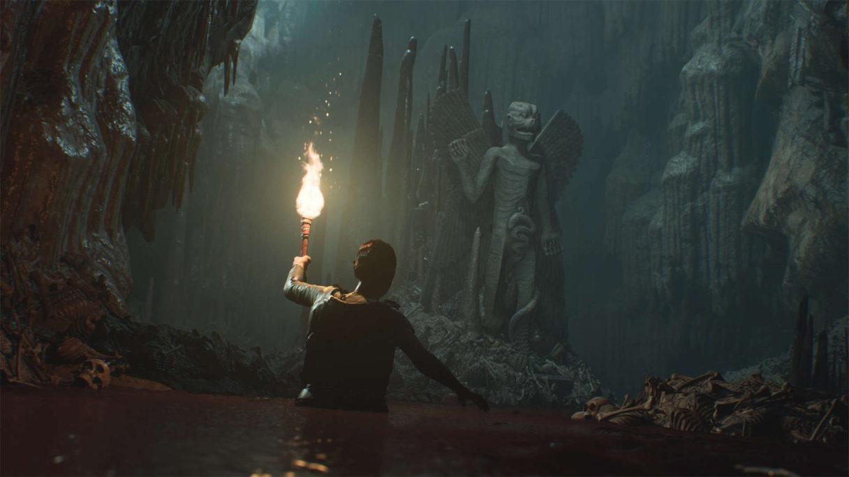 Mężczyzna z pochodnią idzie przez ciemną starożytną jaskinię.