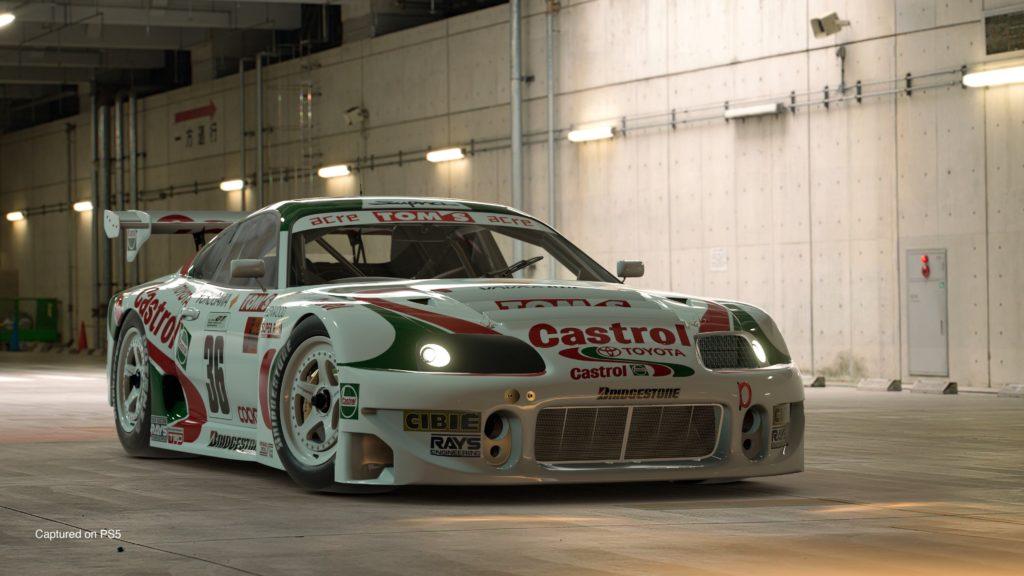Gran Turismo 7 - Toyota Supra GT500 97' (Castrol Tom's) w hangarze. Samochód ma zapalone światła