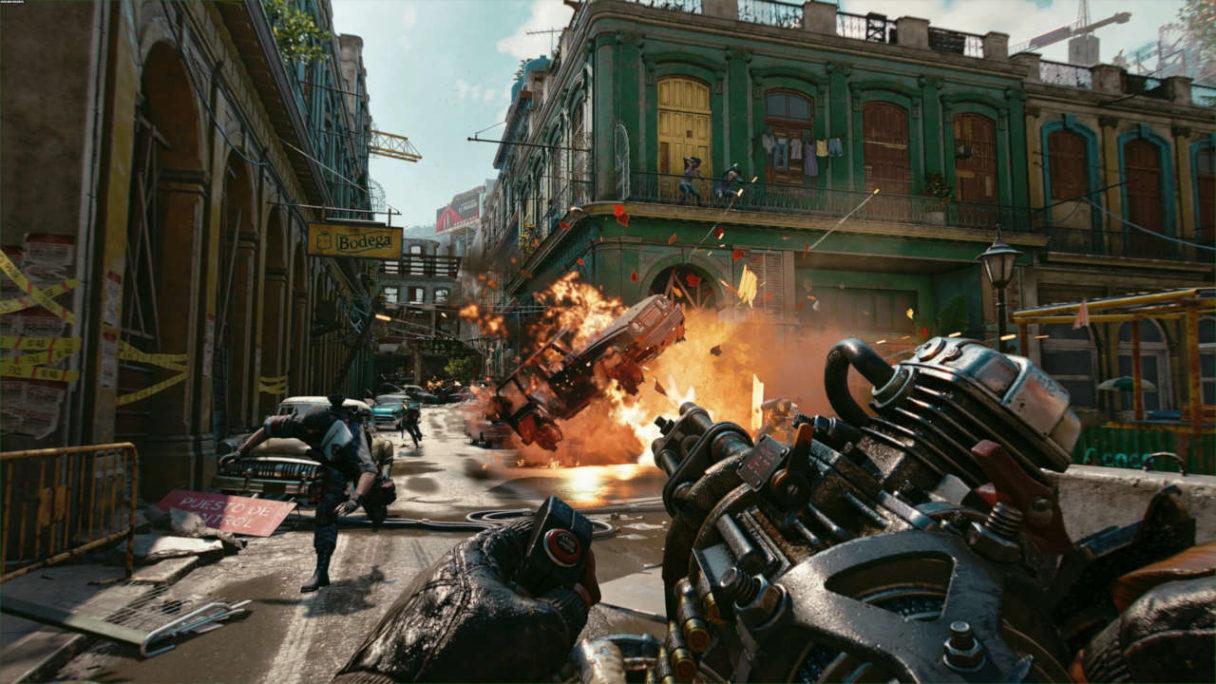 Wymagania sprzętowe - Far Cry 6 - screen z gry przedstawiający strzelaninę w mieście, w tle wybuch