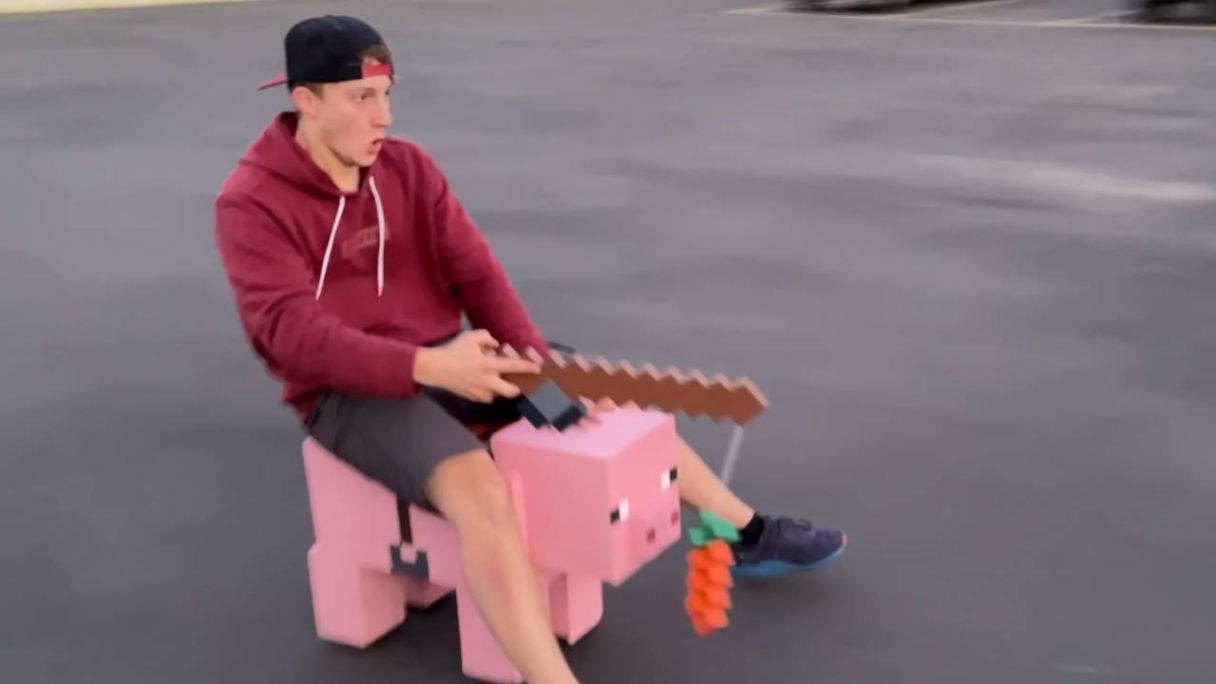 Minecraft - chłopak ujeżdża drewnianą świnię z gry i ma przerażoną minę - PG